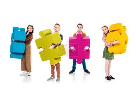 Photo pour Enfants heureux regardant caméra et tenant puzzle pièces sur blanc - image libre de droit