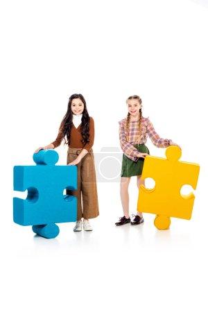 Foto de Niños sonrientes con piezas de rompecabezas mirando a la cámara en blanco - Imagen libre de derechos