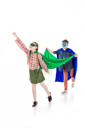 Foto de Boy holding cape of kid in superhero costume posing with outstretched hand On White - Imagen libre de derechos