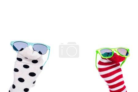 Photo pour Vue recadrée de la personne avec des marionnettes chaussettes colorées et des lunettes de soleil sur les mains isolé sur blanc - image libre de droit