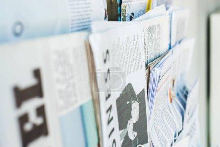 Photo pour Mise au point sélective de différents journaux imprimés sur stand - image libre de droit