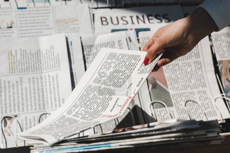 Photo for Partial view of woman taking daily print newspaper from stand - Royalty Free Image