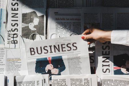 Photo pour Partial view of woman taking daily print business newspaper from stand - image libre de droit