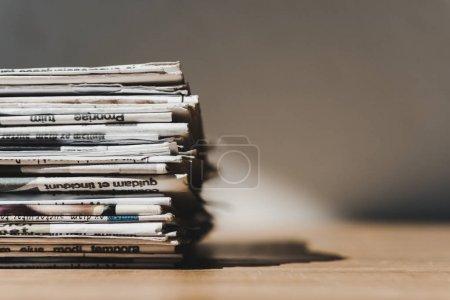 Photo pour Différents journaux imprimés en pile sur une table en bois avec ombre - image libre de droit