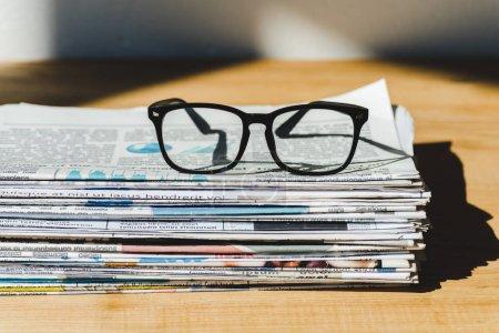Photo pour Différents journaux imprimés en pile sur une table en bois avec des lunettes - image libre de droit