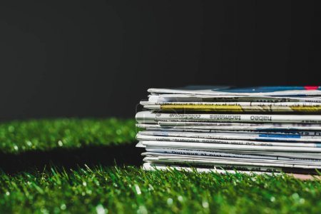 Photo for Stack of different print newspapers on fresh green grass isolated on black - Royalty Free Image