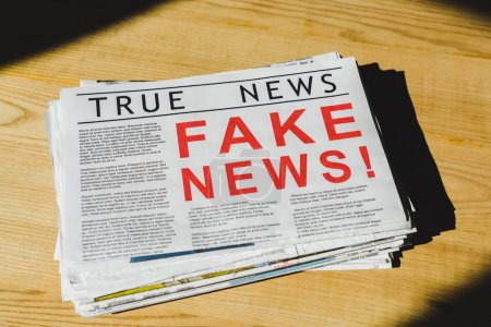 Photo pour Pile of newspapers with fake and true news on wooden table - image libre de droit