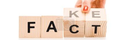 Photo pour Vue recadrée de la femme tenant des blocs de bois avec des faits ou de faux mots isolés sur blanc - image libre de droit