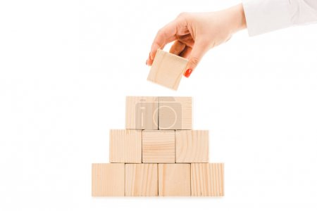 partial view of woman picking up one wooden block with copy space from pyramid isolated on white
