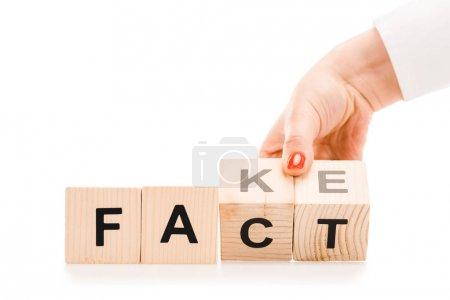 Photo pour Vue partielle de la femme tenant des blocs de bois avec des faits ou de faux mots isolés sur blanc - image libre de droit