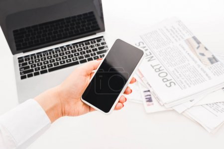 Photo pour Selective focus of woman holding smartphone with blank screen near laptop and  newspapers with sport news - image libre de droit