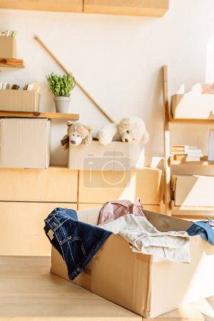 Photo pour Wooden cabinets and cardboard boxes with clothes, books and toys in charity center - image libre de droit