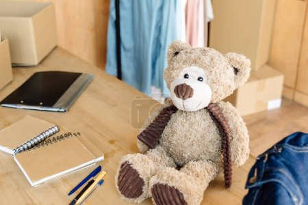 Photo pour Ours en peluche, cahiers, stylos et presse-papiers sur une table en bois dans le centre de charité - image libre de droit