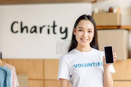 Photo pour Beau bénévole asiatique tenant smartphone avec écran blanc, souriant et regardant la caméra - image libre de droit