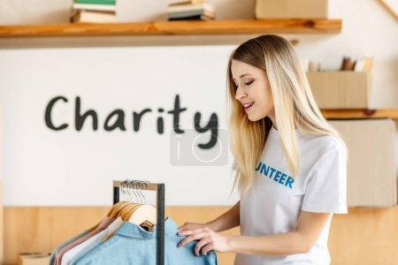 Photo pour Jolie blonde bénévole debout près du rack avec différentes chemises - image libre de droit