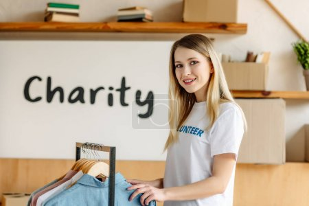 Photo for Beautiful blonde volunteer standing near rack with shirts and looking at camera - Royalty Free Image