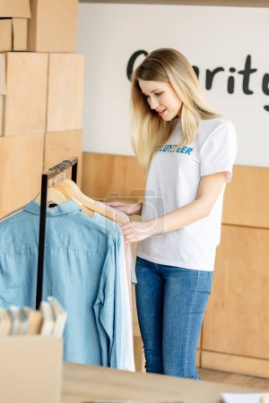 Photo for Pretty blonde volunteer girl standing near rack with different shirts - Royalty Free Image