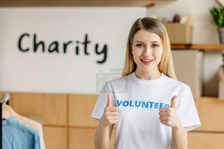 Photo for Beautiful young volunteer showing thumbs up and looking at camera - Royalty Free Image