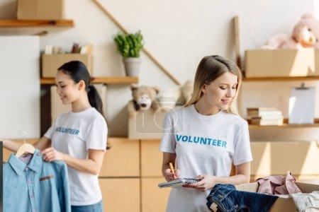 Photo pour Foyer sélectif de la belle jeune écriture volontaire dans le cahier près de la fille asiatique restant par le support avec des vêtements - image libre de droit