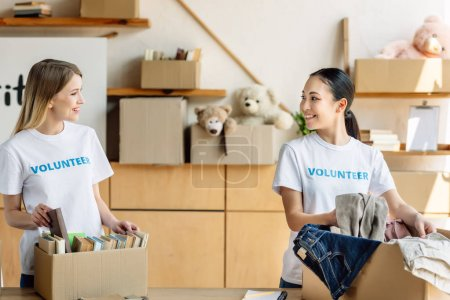 Photo for Two beautiful multicultural volunteers unpacking carton boxes with clothes and books - Royalty Free Image