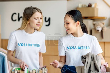 Photo for Two attractive multicultural volunteers unpacking carton boxes with books and clothes - Royalty Free Image