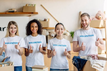 Photo for Group of four smiling young volunteers in white t-shirts with volunteer inscriptions showing thumbs up - Royalty Free Image