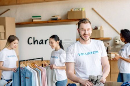Photo for Selective focus of handsome volunteer unpacking carton box with clothes near multicultural girls working in charity center - Royalty Free Image