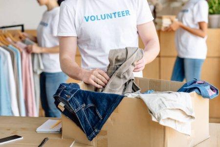 Photo pour Vue recadrée de boîte en carton de déballage volontaire avec des vêtements - image libre de droit