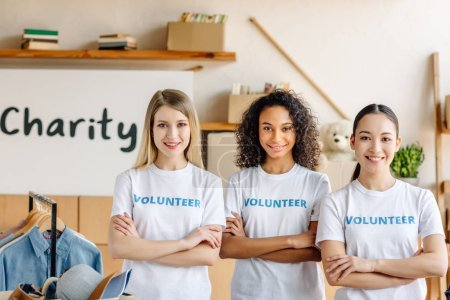 Photo for Three beautiful multicultural volunteer girls with crossed arms smiling and looking at camera - Royalty Free Image