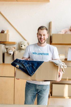 Photo pour Beau, joyeux volontaire retenant la boîte en carton avec des vêtements - image libre de droit