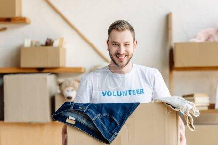 Photo pour Beau jeune volontaire retenant la boîte de carton avec des vêtements, souriant et regardant l'appareil-photo - image libre de droit