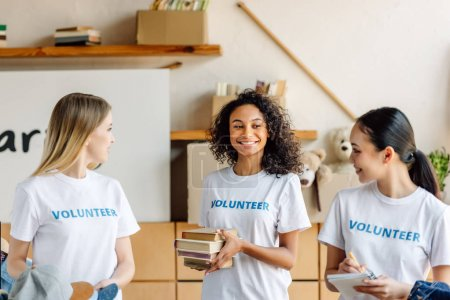 Photo for Pretty, multicultural girls in white t-shirts with volunteer inscriptions smiling and looking at each other - Royalty Free Image