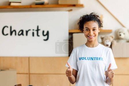 Foto de Chica voluntaria afroamericana bastante mostrando los pulgares hacia arriba y mirando a la cámara - Imagen libre de derechos