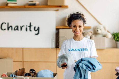Photo for Pretty african american volunteer holding clothes, smiling and looking at camera - Royalty Free Image
