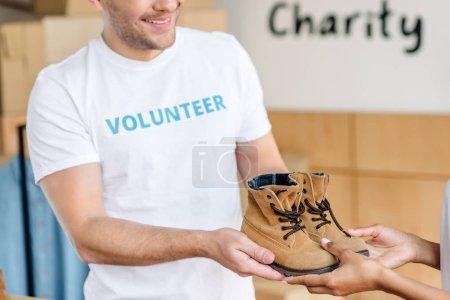 Photo pour Vue recadrée de deux bénévoles multiculturels tenant des chaussures pour enfants - image libre de droit