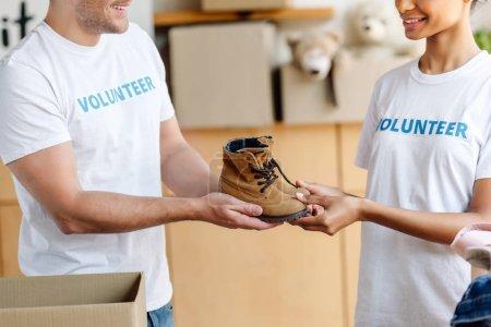 Photo pour Vue recadrée de deux volontaires multiculturels retenant des chaussures d'enfants dans le centre de charité - image libre de droit