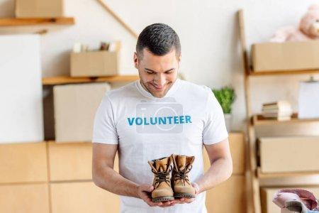 Photo pour Beau, jeune homme dans le t-shirt blanc avec l'inscription volontaire retenant des chaussures d'enfants - image libre de droit