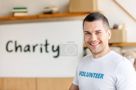 Photo pour Beau, bénévole souriant debout près de la plaque avec l'inscription de charité - image libre de droit
