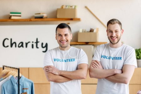 Photo for Two handsome volunteers standing with crossed arms and looking at camera - Royalty Free Image