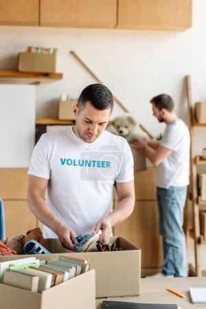 Photo pour Focus sélectif de beau bénévole déballage boîte carton avec des chaussures - image libre de droit