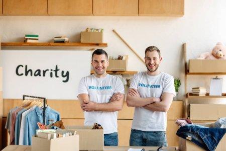 Foto de Two cheerful, handsome volunteers standing with crossed arms and looking at camera - Imagen libre de derechos