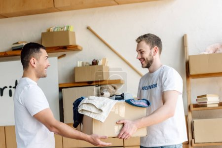 Photo for Two good-looking, smiling volunteers holding cardboard box with clothes in charity center - Royalty Free Image