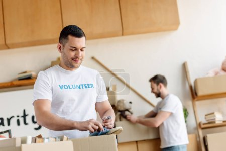 Photo for Selective focus of handsome volunteer unpacking cardboard box with footwear - Royalty Free Image