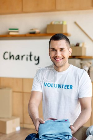 Photo pour Handsome, smiling volunteer holding clothes and looking at camera in charity center - image libre de droit