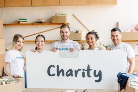 Photo pour Cinq jeunes bénévoles multiculturels tenant une pancarte avec une inscription de charité - image libre de droit