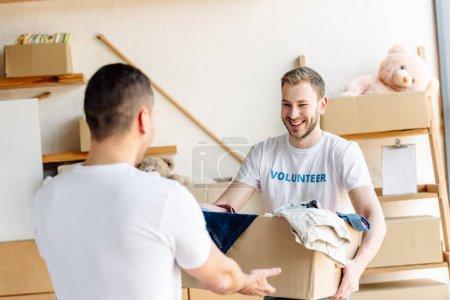 Photo pour Deux jeunes volontaires retenant la boîte en carton avec des vêtements dans le centre de charité - image libre de droit