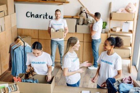 Foto de Group of young multicultural volunteers in white t-shirts with volunteer inscriptions working in charity center - Imagen libre de derechos