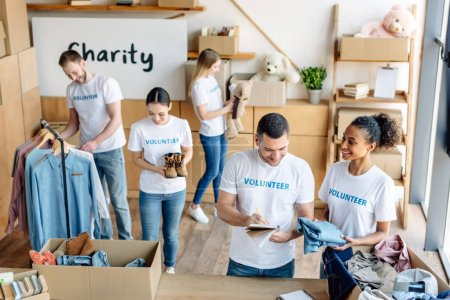 Photo pour Jeunes bénévoles multiculturels joyeux en t-shirts blancs avec inscriptions bénévoles travaillant dans un centre caritatif - image libre de droit