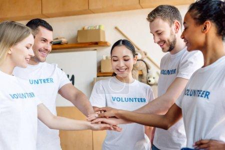 Photo pour Cinq jeunes bénévoles multiculturels souriant et se tenant la main dans un centre de charité - image libre de droit