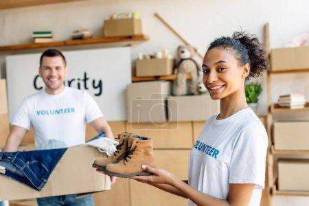 Foto de Enfoque selectivo de bastante afroamericano voluntario sosteniendo zapatos de niños cerca de hombre guapo con caja de cartón - Imagen libre de derechos